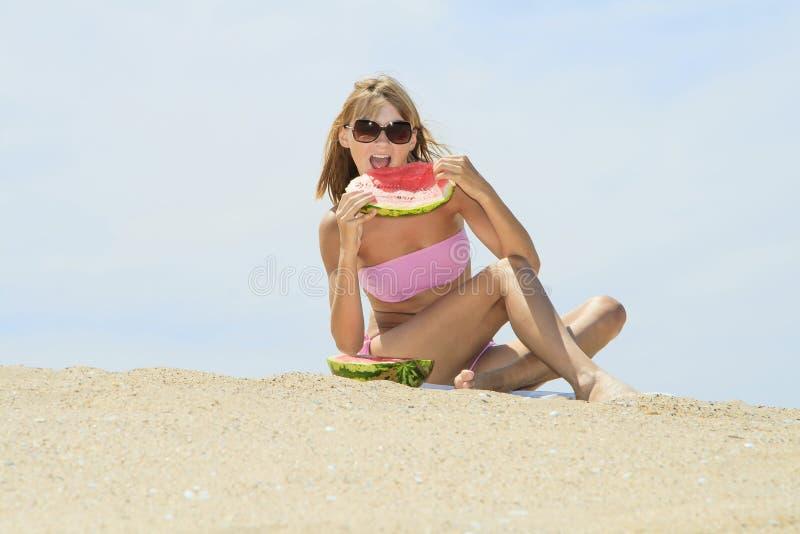 pastèque femelle de consommation sur la plage image stock