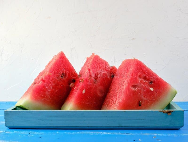 pastèque ronde rouge mûre coupée en tranches de triangles avec des graines photos stock