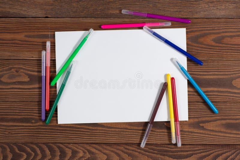 Pastéis coloridos e uma folha de papel a madeira do caderno imagens de stock