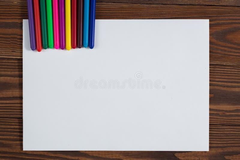 Pastéis coloridos e uma folha de papel a madeira do caderno imagem de stock