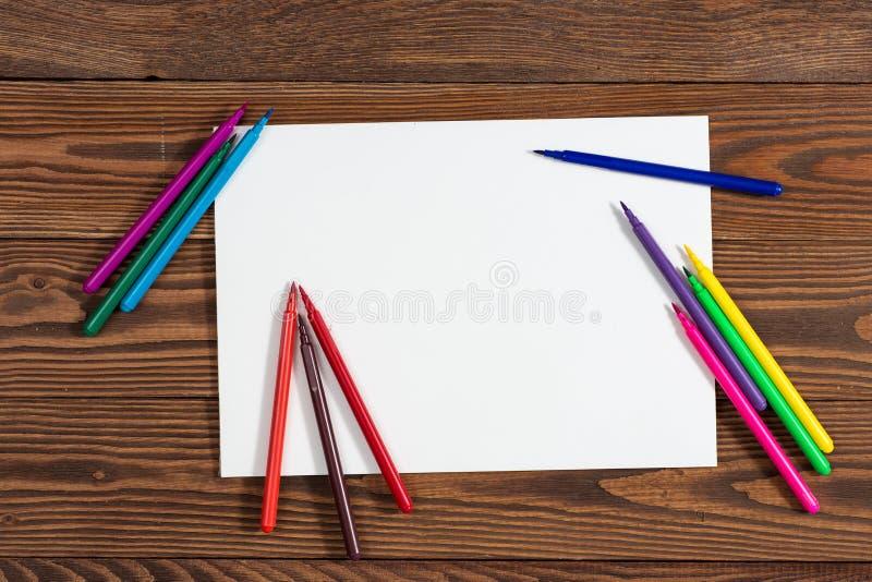 Pastéis coloridos e uma folha de papel a madeira do caderno fotos de stock royalty free