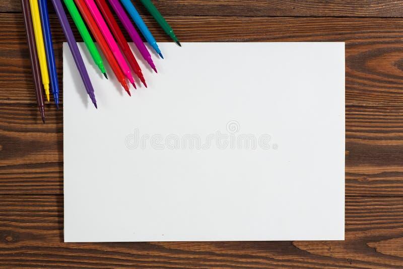 Pastéis coloridos e uma folha de papel a madeira do caderno foto de stock royalty free