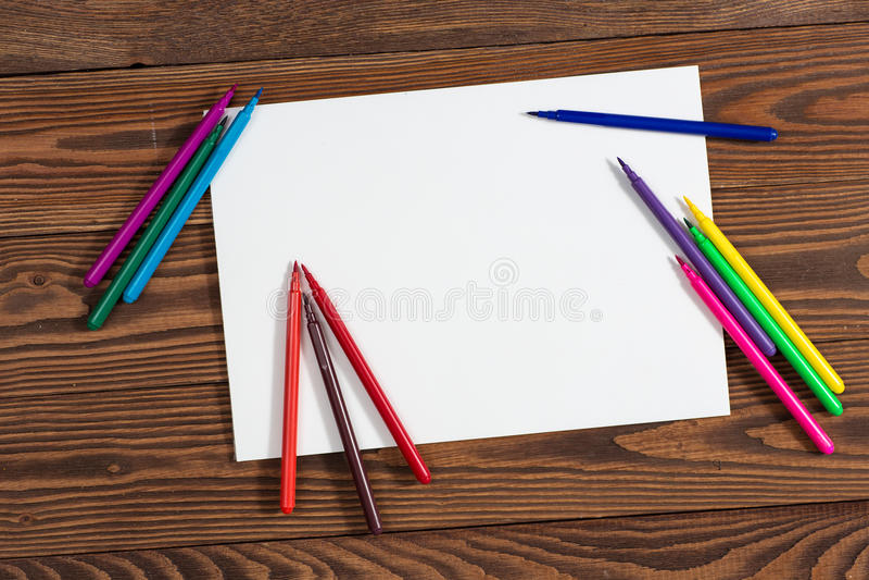 Pastéis coloridos e uma folha de papel a madeira do caderno fotografia de stock