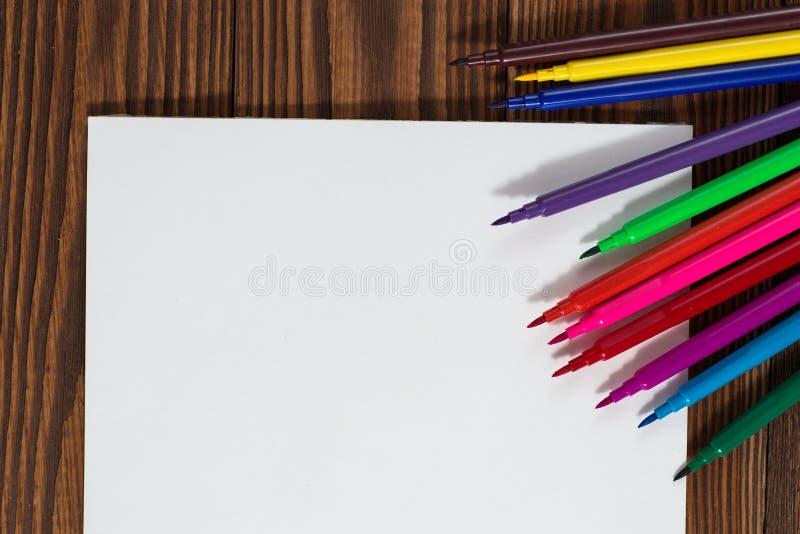 Pastéis coloridos e uma folha de papel a madeira do caderno fotografia de stock royalty free