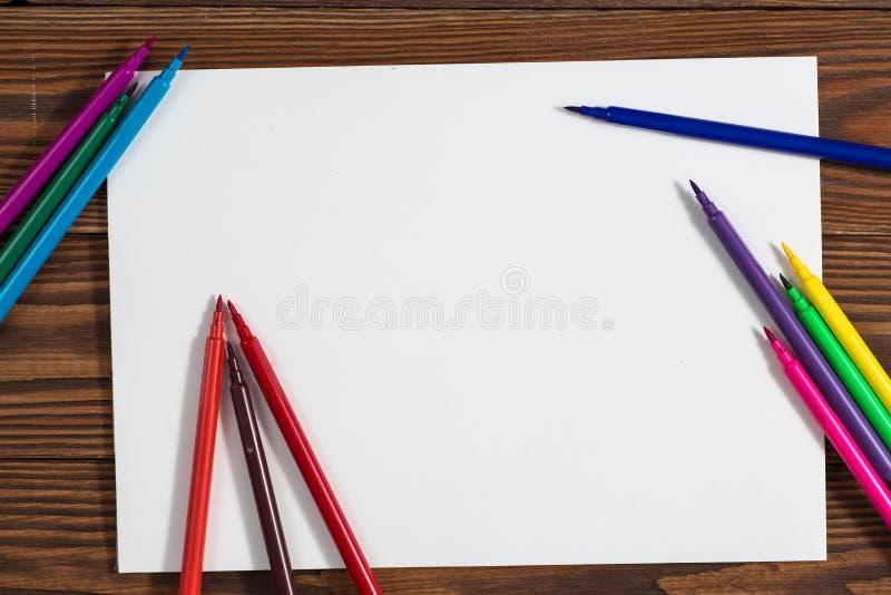 Pastéis coloridos e uma folha de papel a madeira do caderno fotos de stock