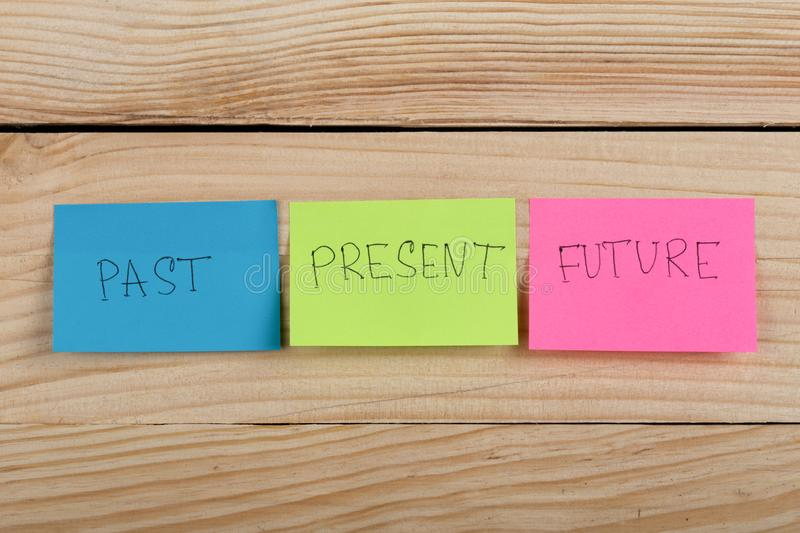 """Past, present, future"", the phrase is written on colorful stickers on wooden desk. Business choice - ""Past, present, future"", the phrase is royalty free stock image"