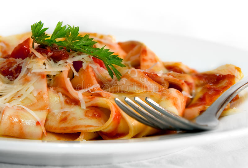 Pasta. Tomato pasta on a plate with a fork stock images