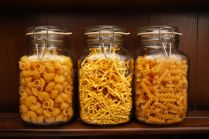 Pasta. 3 pasta jars with pasta on wooden shelf stock image