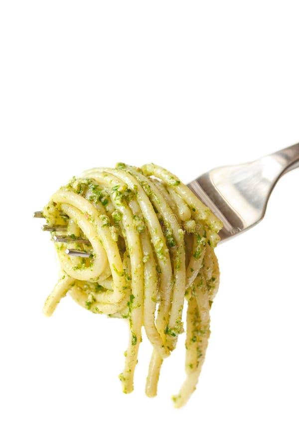 Pasta. Fresh hot spaghetti with pesto on a fork stock image