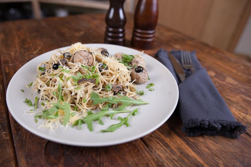 Pasta with anchovies and black olives stock image