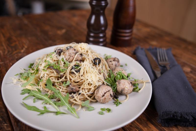 Pasta with anchovies and black olives stock photos