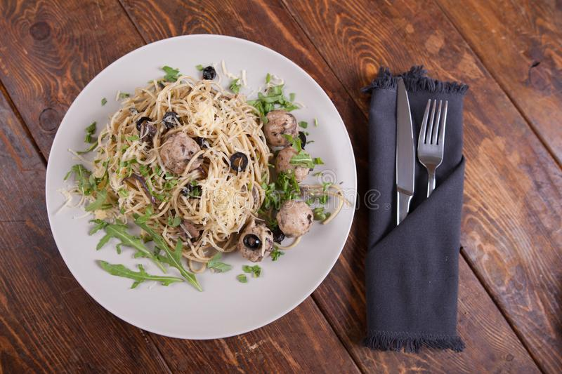 Pasta with anchovies and black olives stock photography