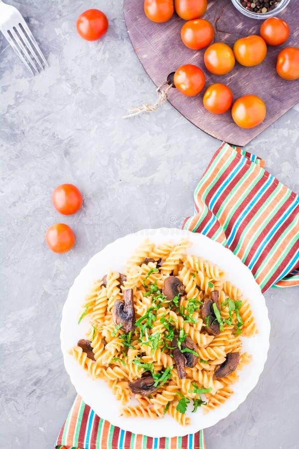 Pasta appetitosa con i funghi fritti, il pomodoro e le erbe fresche fotografia stock