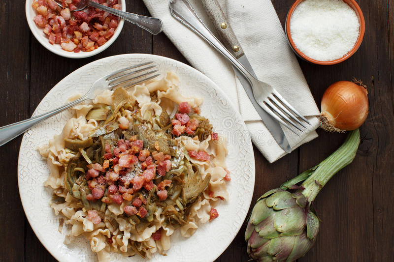 Pasta with artichokes and bacon royalty free stock image