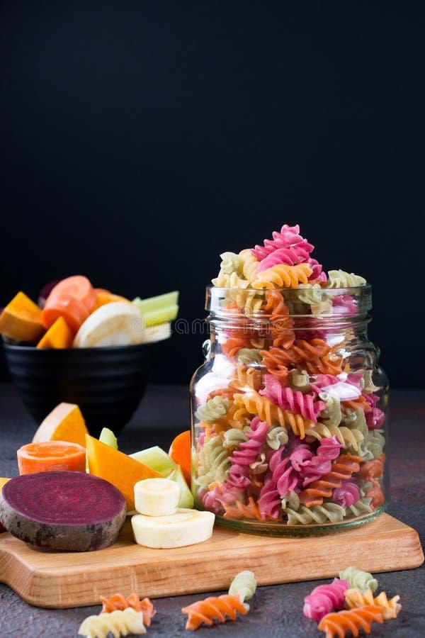 Pasta asciutta di fusilli del riso dalle verdure in un barattolo di vetro I suoi coloranti vegetali naturali sedano, barbabietola fotografie stock