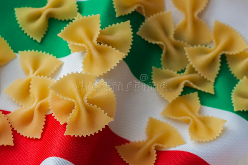 Pasta asciutta, maccheroni su un fondo del tessuto nei colori dell'italiano tricolore Cucina italiana tradizionale Primo piano fotografia stock