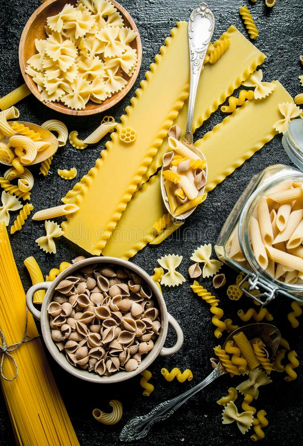 Pasta background. Different types of dry pasta in the pot and bowl stock image