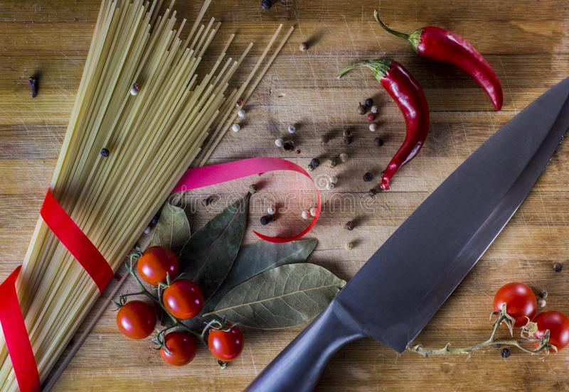 Pasta background. Dry pasta with hot pepper, tomatoes, onion, garlic. On a black wooden background. Spaghetti and royalty free stock photo