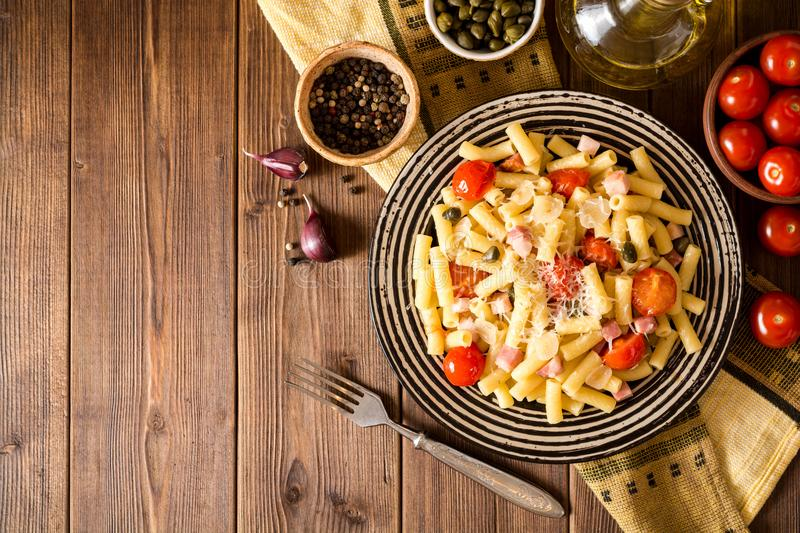 Pasta with bacon, garlic, tomatoes, capers and parmesan cheese in plate on dark wooden background. stock images