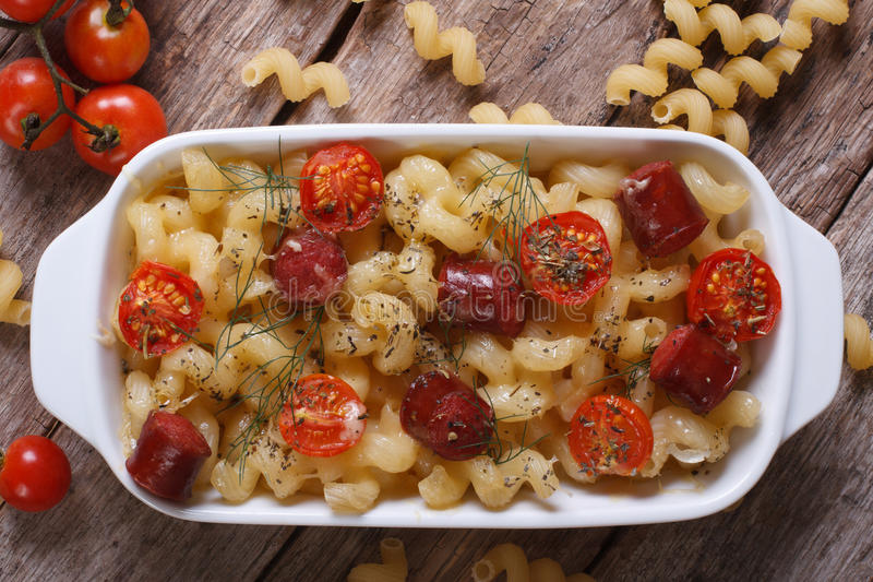 Pasta baked with cherry tomatoes and sausages top view stock images