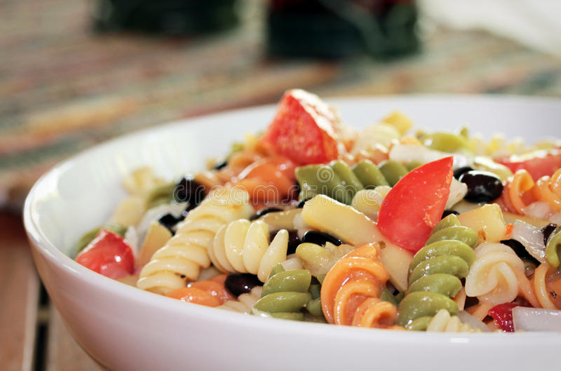 Pasta Bean Salad. A corkscrew pasta salad with black beans and tomatoes in a white serving bowl royalty free stock photos