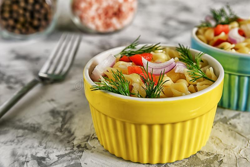 Pasta with bell peppers, onions and dill. A small yellow bowl with vegetarian food. Healthy dinner without meat. Light photo stock image