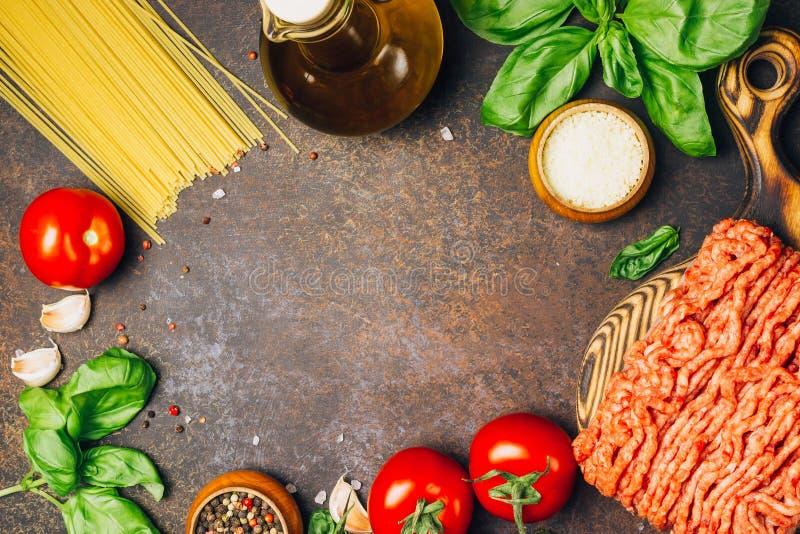 Pasta bolognese che cucina concetto: carne tritata cruda, pomodori, pasta, parmigiano, aglio, basilico, olio d'oliva fotografie stock