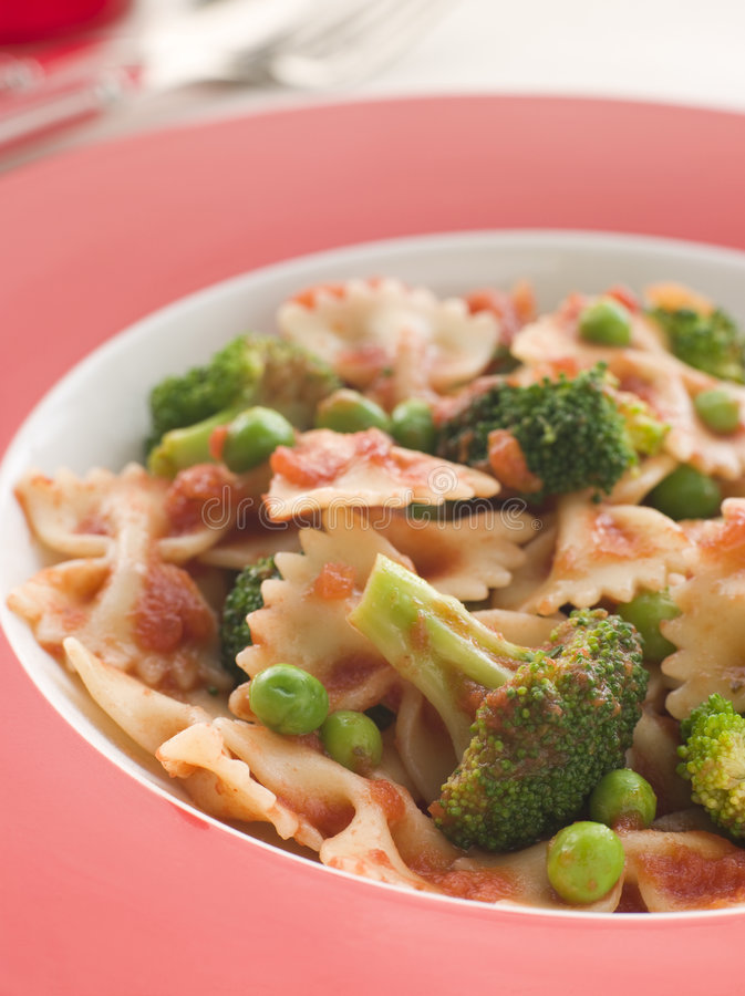Pasta Bows with Tomato Sauce Broccoli and Peas stock photography