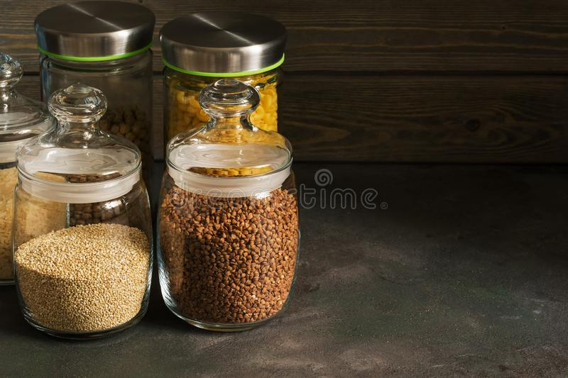 Pasta, buckwheat, quinoa and chickpeas in a glass jar on a dark rustic background. Selective focus, copy space stock photos