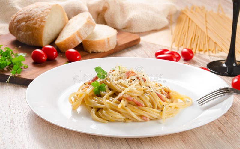 Pasta Carbonara with bacon on a white plate, wooden table stock photography