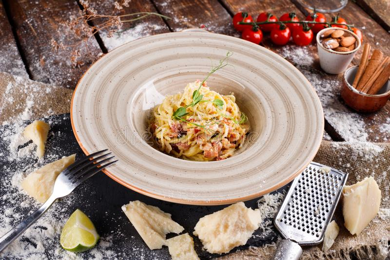 Pasta Carbonara with Parmesan on a white plate. Restaurant food at the wooden table royalty free stock images