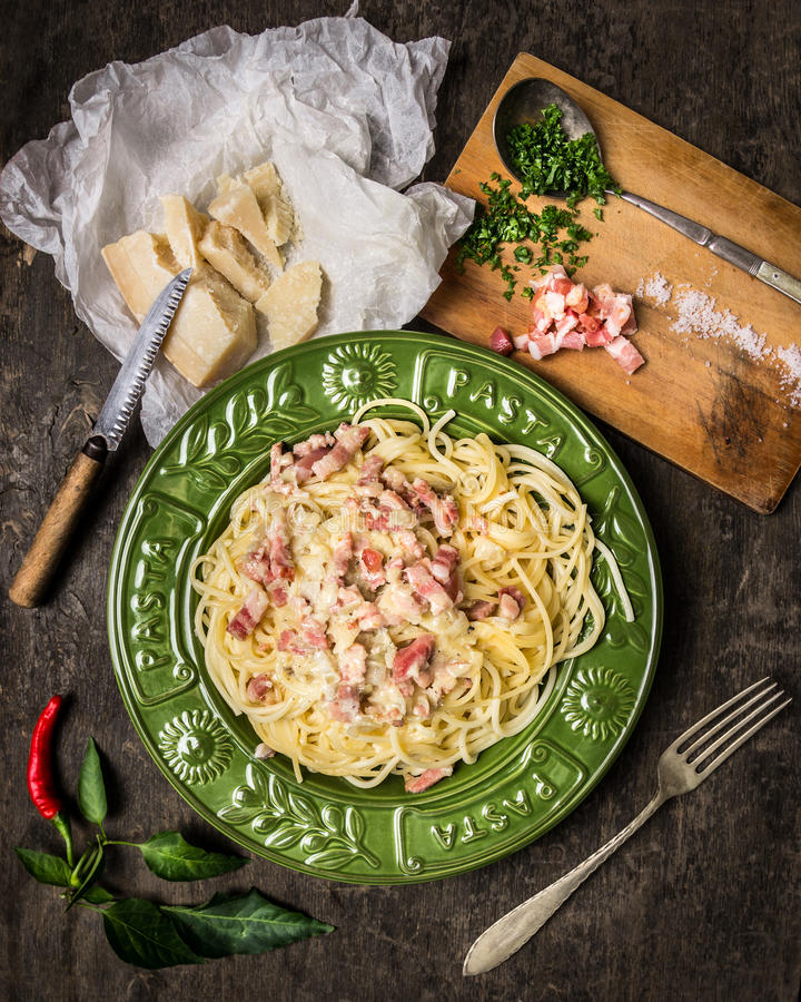 Pasta Carbonara in piatto, in parmigiano, in spezie e nei condimenti verdi fotografie stock