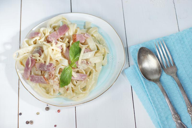 Pasta carbonara on a plate with cutlery near the plate, standing on a wooden white table royalty free stock photography