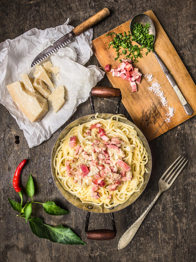 Pasta carbonara in vintagen pan with parmesan cheese ,spices and herbs on cutting board royalty free stock photos
