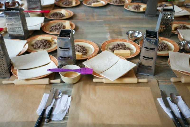 Pasta, carne tajada frita y utensilios para las clases de cocina en la tabla de madera, concepto de clase de cocina fotografía de archivo libre de regalías