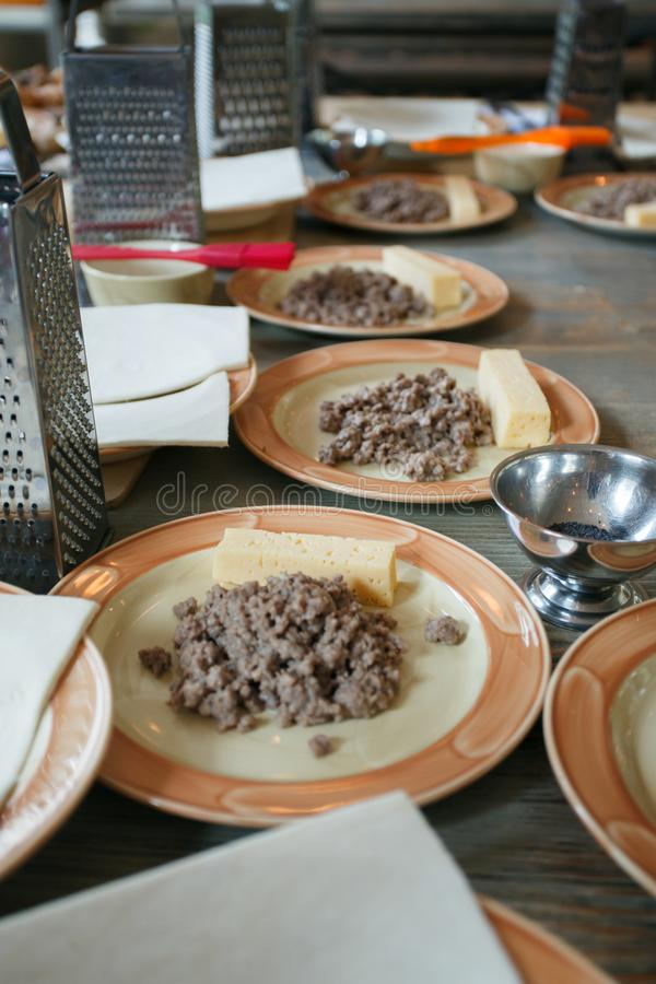 Pasta, carne tajada frita y utensilios para las clases de cocina en la tabla de madera, concepto de clase de cocina imagenes de archivo