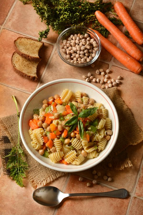 Pasta with chickpeas, carrots and celery stock images