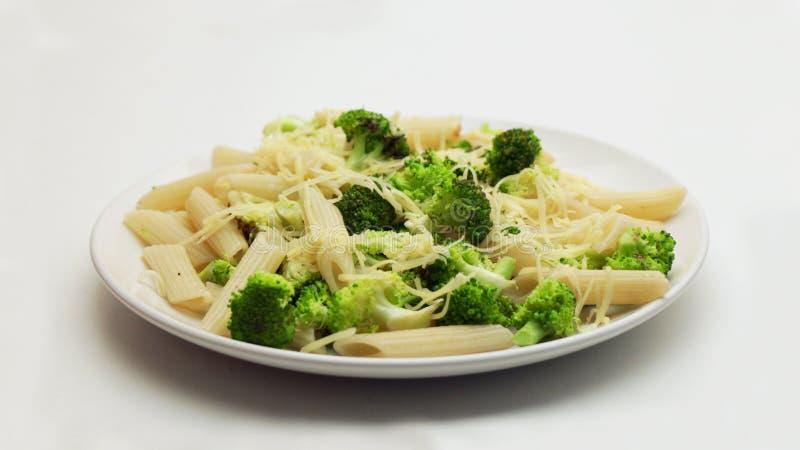 Pasta con i broccoli ed il formaggio grattugiato su un piatto bianco immagini stock