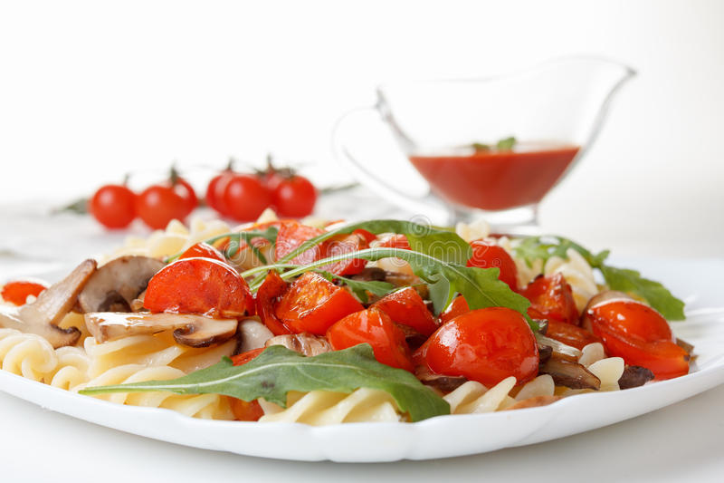 Pasta con i funghi, i pomodori ciliegia e la salsa al pomodoro, alimento italiano closeup fotografia stock
