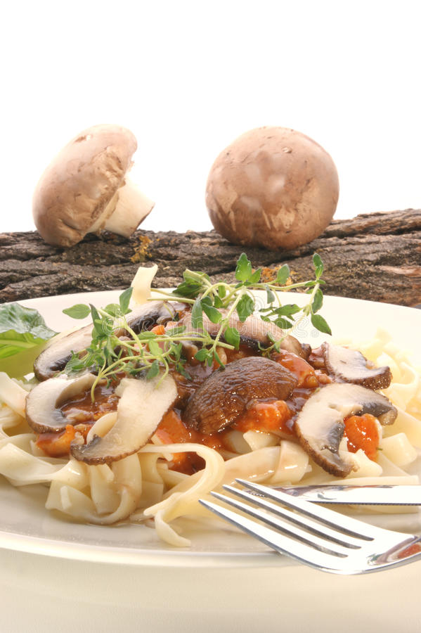 Pasta con il fungo e le erbe su una zolla fotografia stock