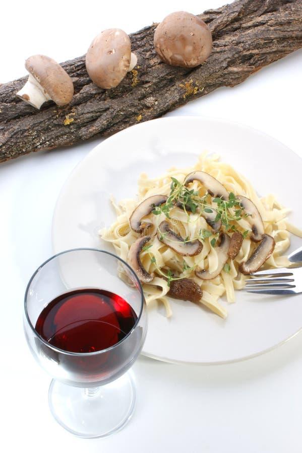 Pasta con il fungo e le erbe su una zolla bianca fotografia stock libera da diritti