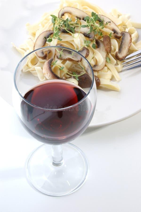 Pasta con il fungo ed il vino rosso fotografia stock libera da diritti