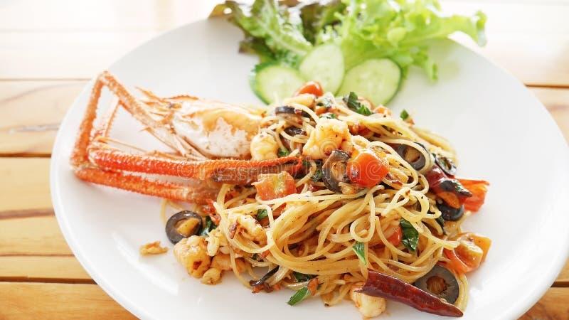 Pasta con il gamberetto, le olive, i pomodori ed i peperoncini rossi giganti sul BAC di legno immagine stock libera da diritti