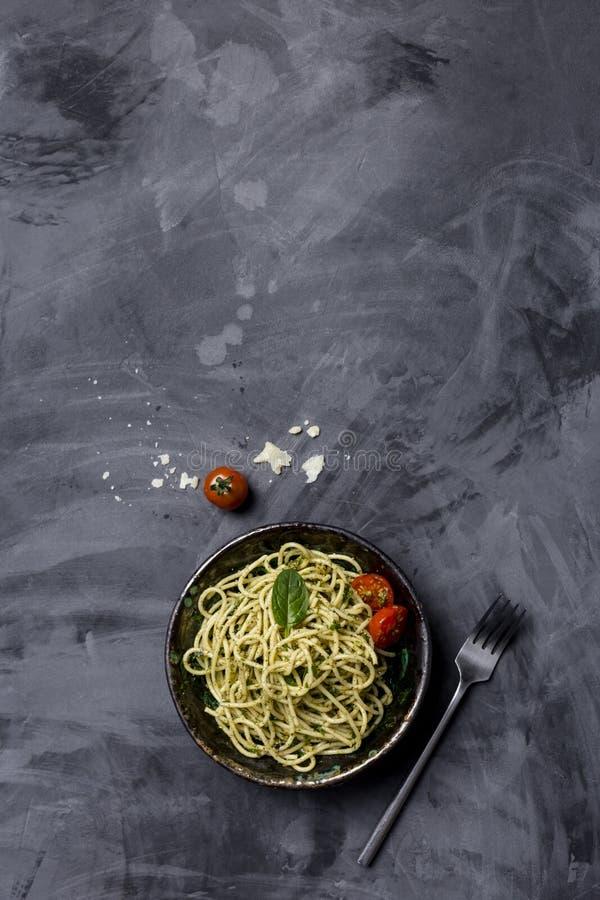 Pasta con il pesto e pomodori ciliegia a fondo nero, vista superiore immagine stock