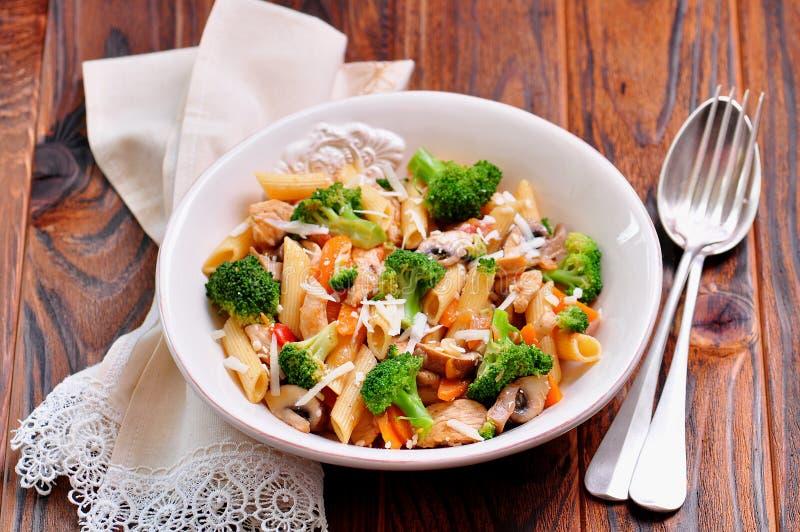 Pasta con il pollo, i broccoli, le carote, i pomodori ed il parmigiano immagini stock libere da diritti