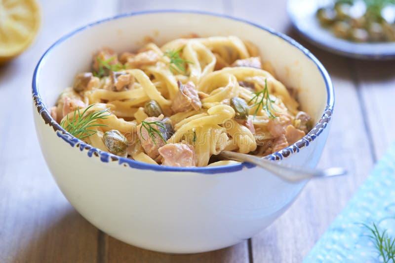 Pasta con il salmone affumicato ed i capperi in salsa crema immagine stock