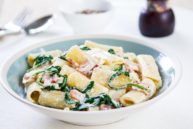 Pasta con la salsa crema degli spinaci e del bacon fotografia stock