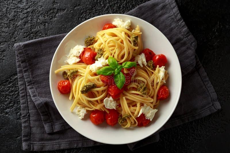 Pasta con la salsa verde di pesto, i pomodori ciliegia arrostiti ed il formaggio della mozzarella in piatto bianco su fondo rusti fotografie stock libere da diritti