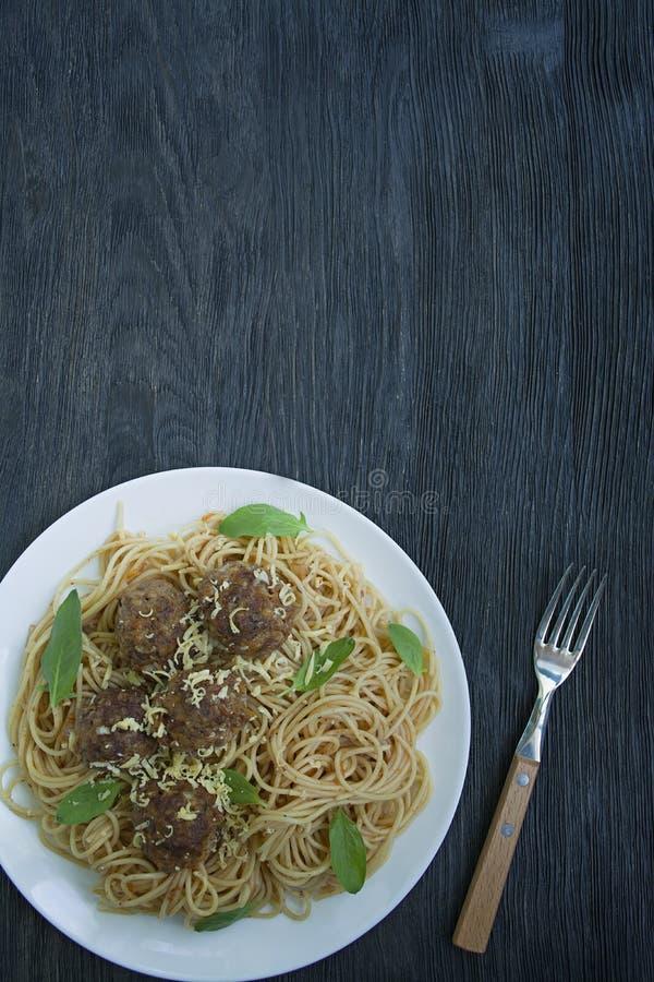Pasta con le polpette ed il prezzemolo in salsa al pomodoro Priorit? bassa di legno scura Vista da sopra immagine stock libera da diritti