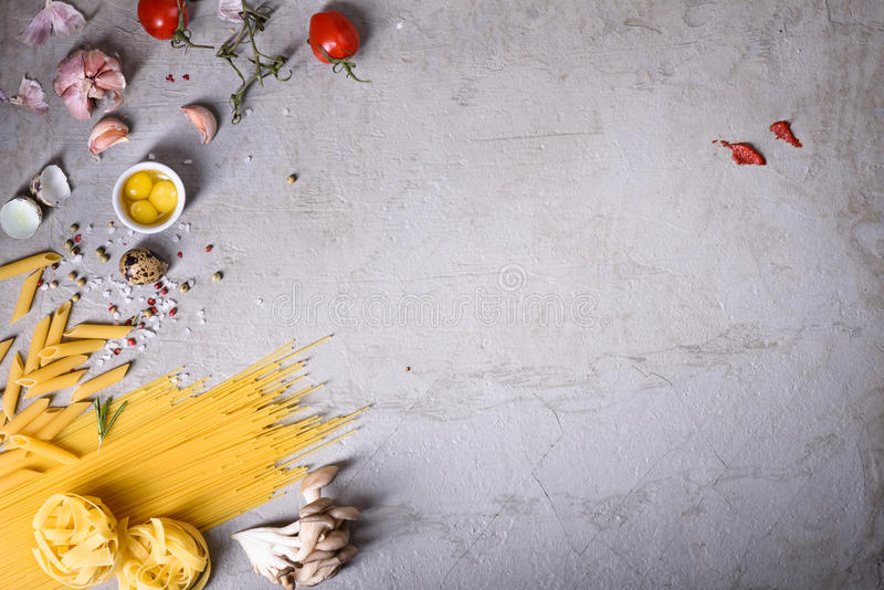 Pasta with cooking ingredients on grey countertop. Italian recipe. View from above, copy space. Pasta with cooking ingredients on grey countertop. Italian royalty free stock photos
